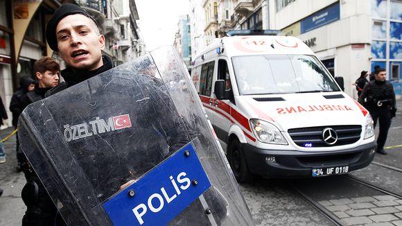 Poliisi ohjaa ambulanssia pommi-iskun tapahtumapaikalta Istanbulissa.