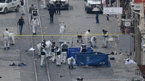Valkoisiin suojapukuihin pukeutuneita henkilöitä tutkimassa räjähdyspaikkaa.