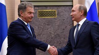 Tummapukuiset, kravattikaulaiset Niinistö ja Putin kättelevät vienosti hymyillen. Taustalla näkyy huoneen seinää ja Suomen ja Venäjän liput.