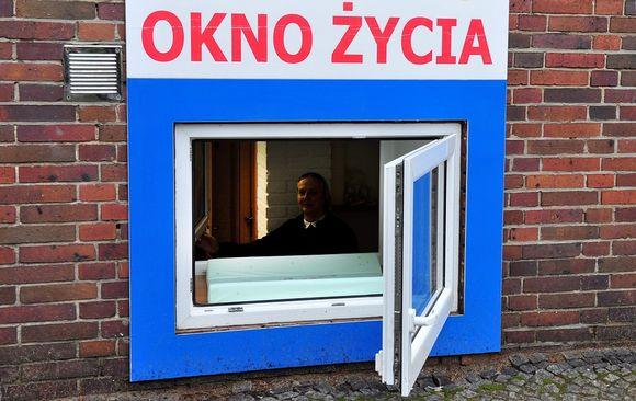 """Sinikehyksinen lasiluukku tiiliseinässä. Yläpuolella puolankielinen kyltti, """"elämän ikkuna""""."""