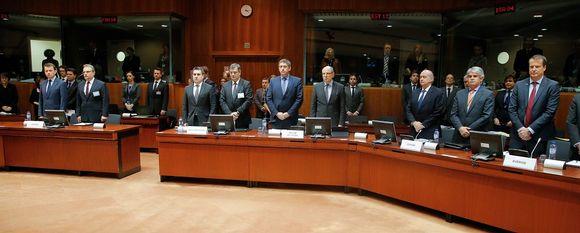 Kokousedustajat seisovat pöytiensä takana istuntosalissa.