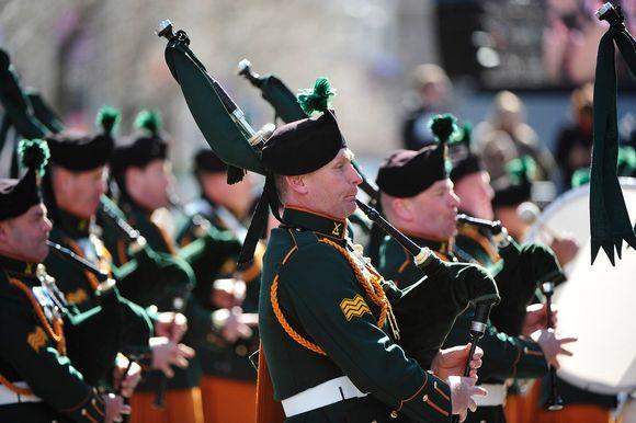 Säkkipillejä soittavia sotilaita marssimassa vihreissä juhlaunivormuissa.