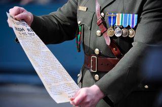 Upseeri pitelee paperiliuskaa. Rinnassa useita kunniamerkkejä.