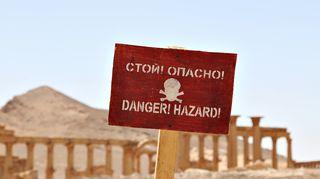 Varoituskyltti hengenvaarasta. Isis-järjestö jätti vetäytyessään räjähteitä Palmyran rauniokaupunkiin. Venäläiset sotilaat ovat raivanneet alueelta miinoja.