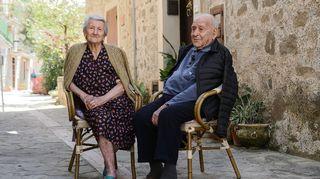 Amina Fedullo ja Antonio Vassallo nauttivat raikkaasta ulkoilmasta asuntonsa edustalla Acciarolin kylässä. Vanha pariskunta istuu tuoleilla.