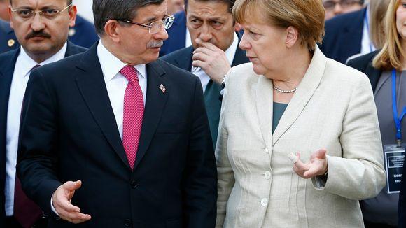 Turkin eroava pääministeri kävelee Angela Merkelin kanssa.