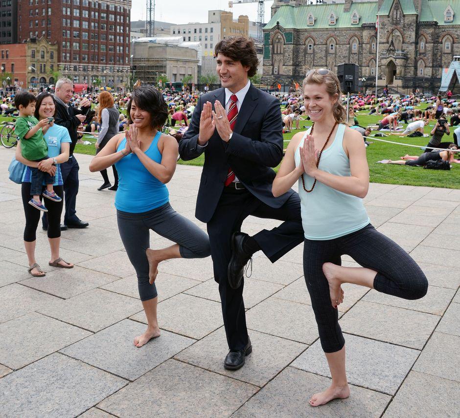 Tummaan pukuun pukeutunut Justin Trudeau koukistaa polveaan jooga-asentoon, vierellä kaksi voimisteluasuista naista tekee samaa.