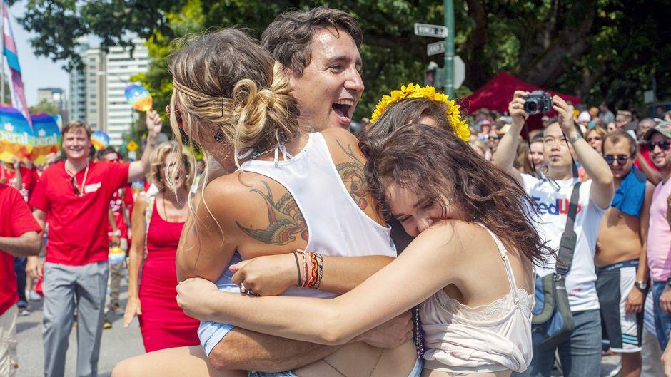 Kolme naista halaa Justin Trudeauta, taustalla ihmiset ottavat tilanteesta kuvia.