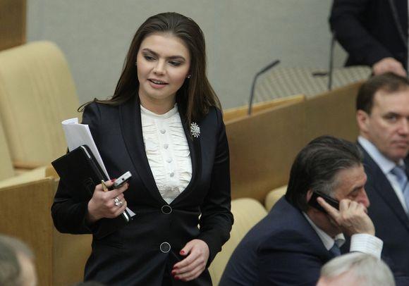 Alina Kabajeva seisoo penkin edessä Venäjän parlamentin alahuoneen istuntosalissa. Kädessä hänellä on kännykkä, tabletti ja papereita.