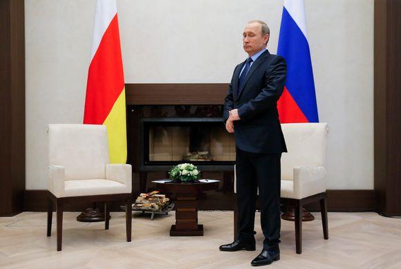 Putin seisoo huoneessa, jossa on Venäjän ja Etelä-Ossetian liput, kaksi nojatuolia ja takka.