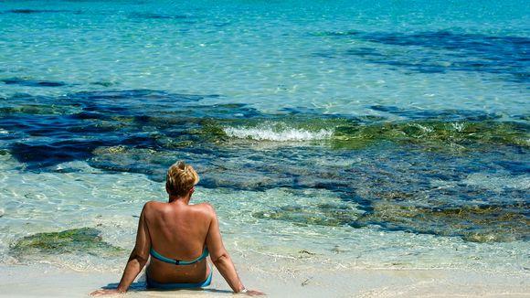Bikineihin pukeutunut nainen istuu selin hiekassa, edessä turkoosinsininen meri.
