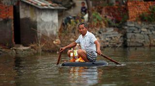 Mies soutaa itsetehdyllä lautalla tulvan valtaamassa Xinhuan kylässä Kiinassa.