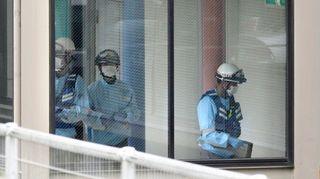 Japanissa Sagamiharassa Tokion lähellä viranomaiset tutkivat hoitolaitosta, jossa mies puukotti kuoliaaksi ainakin 15 ihmistä. Kolme ihmistä näkyy suuren ikkunan takana. Heillä on kypärät päässään, suojakäsineet käsissään ja hengityssuojaimet kasvoillaan.