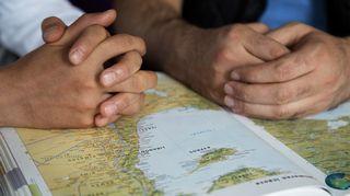 Kahden henkilön kädet karttakirjan päällä.