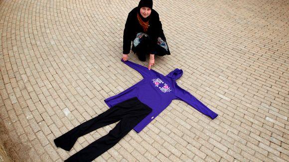 Kuvassa nainen esittelee violetti-mustaa burkinia. Huppumallinen tunika on violetti ja siihen kuuluvat mustat housut.
