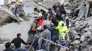 Pelastustyöntekijät kantoivat maanjäristyksessä loukkaantuneen naisen pois raunioista.