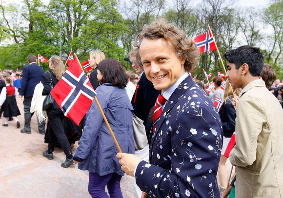 Nuori mies heiluttaa iloisesti Norjan lippua kulkueessa Norjan kansallispäivänä.
