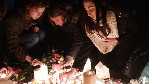 Kolme naista sytyttää kynttilöitä