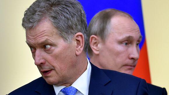 Niinistö katsoo kuvassa vasemmalle ja Putin hänen takanaan oikealle. Taustalla näkyy Venäjän lippu.