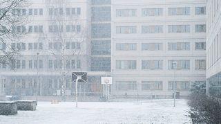 Lunta sataa talojen ympäröimälle koripallokentälle.