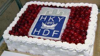 """Video: Täytekakku, jonka päällä on nähtävissä teksti """"HKY - 1895 - HDF""""."""