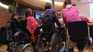 Video: Seminaariin osallistujia istumassa pyörätuoleissa selin kameraan.