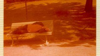 Mies makaa puiston penkillä