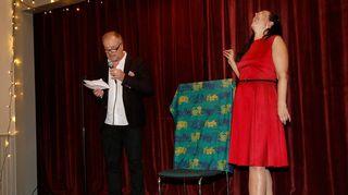 VPK-talon näyttämöllä Matti Rönkä puhuu mikrofoniin ja Johanna Vuoksenmaa nauraa ääneen. Heidän välissään on kankaalla peitetty taulu.