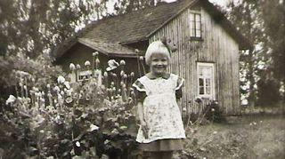 Vuonna 1953 otetussa valokuvassa Pepi Reinikainen on 4-vuotias ja seisoo kotitalonsa pihapiirissä Pohjois-Karjalan Valtimossa.