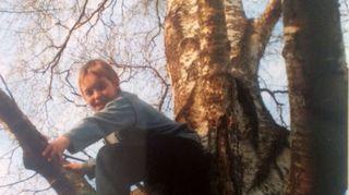 """Kuvassa Niina Hakalahden Mitja-poika on kotitalon puussa. """"Lapset ovat meidän yläpuolella, he elävät meitä kauemmin, me aikuiset katselemme heidän loittonemista, kun he aloittavat oman elämänsä."""""""