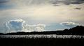 Kuvassa on järvimaiseman yllä monenlaisia pilviä.