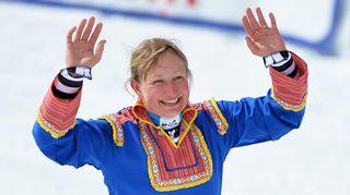 Tanja Poutiainen heiluttaa lapinpuvussa.