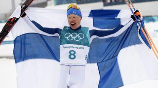 Iivo Niskanen juhlii olympiavoittoa Suomen lipun kanssa.