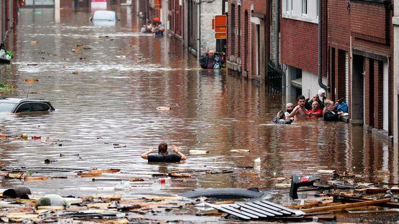 Ihmiset kahlaavat kadulla kainaloihin saakka ulottuvassa tulvavedessä.