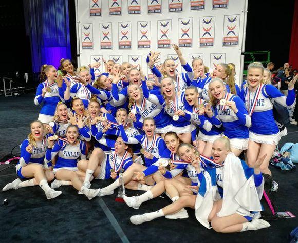 Suomen naisten cheerleadingin maajoukkue tuulettaa ryhmäkuvassa.