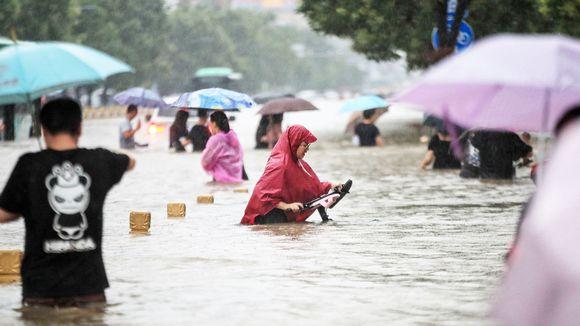 Ihmiset kahlaavat kadulla tulvavedessä.