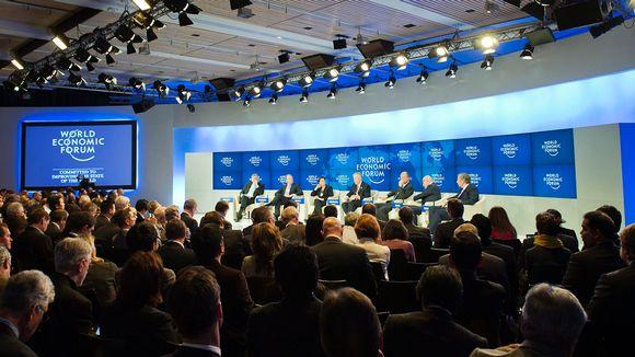 Paneelikeskustelijoita lavalla ja yleisöä talousfoorumissa.