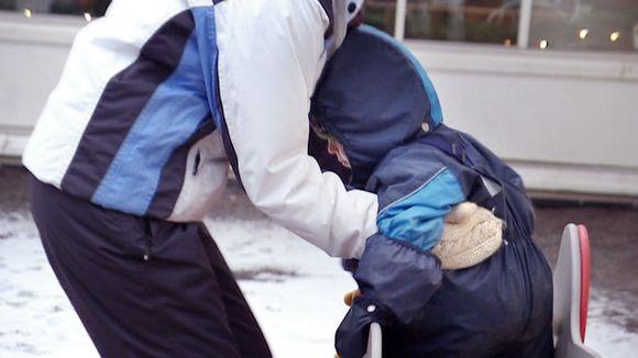 Lastentarhanopettaja nostaa lasta päiväkodin pihalla.