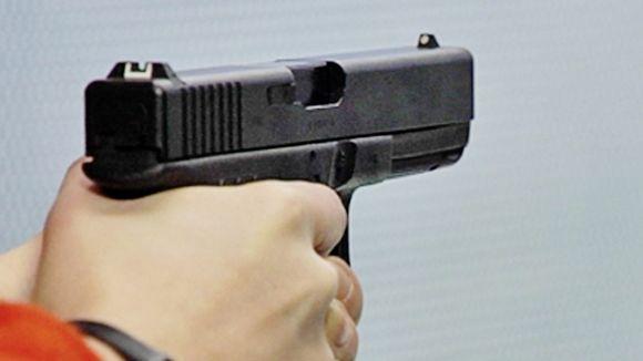 Henkilö pitää asetta kädessään.