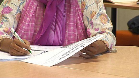 maahanmuuttaja, paperi ja kynä käsissään