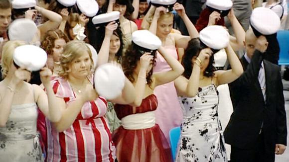 Ylioppilaat laittavat ylioppilaslakin päähänsä lukion lakkiaisjuhlassa.