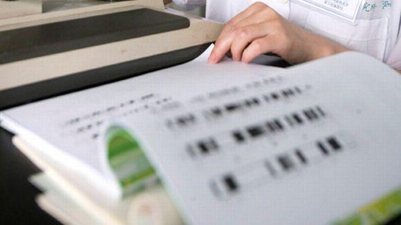Tutkija selaa tulostetta ihmisen geenikartasta.