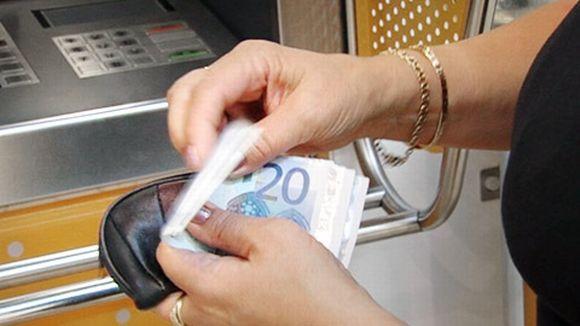 Nainen laskee rahojaan pankkiautomaatilla.