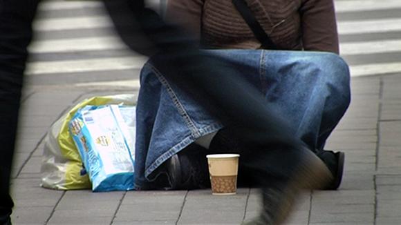 Kerjäläinen istuu kadulla pahvimuki edessään.