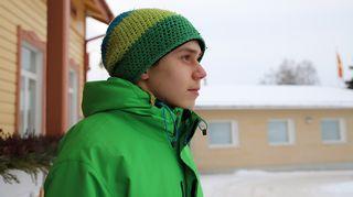 Vihreäraidalliseen pipoon ja vihreään takkiin pukeutunut 16-poika katsoo tulevaisuuteen