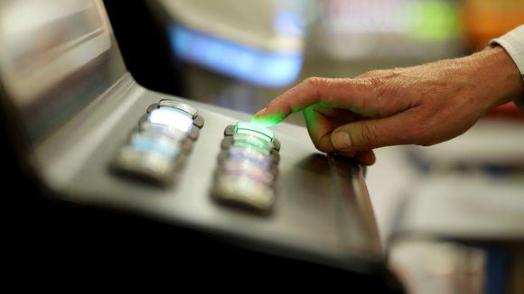 Sormi rahapeliautomaatin napilla.