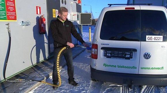 Mies tankkaa kaasuautoa