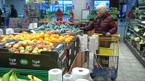 Nainen valitsee salaattia kaupan hedelmä ja vihannes osastolla.
