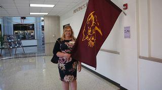 Maija Heikkilä amerikkalaiskoulun käytävällä koulun lipun ääressä