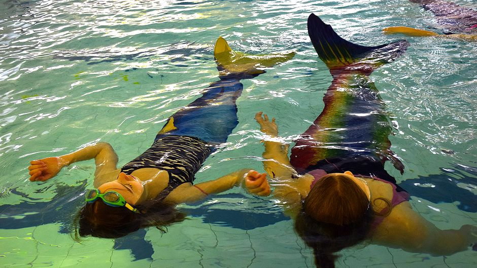 Kaksi merenneitoa kelluu uima-altaassa